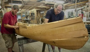 Schuyler Thomson (right) and assistant Frank Christinat work on a new canoe in Thomson's shop.