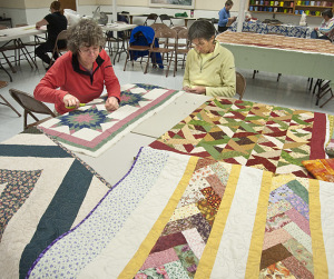 Quilters Lisa Mitchel and Susan Diggle cutting patterns. Photos by Bruce Frisch.