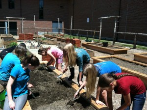 Sixth grade students at Botelle plant their first crop in one of the raised beds.